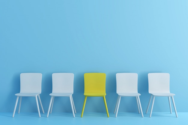 Выдающийся желтый стул среди голубого стула. стулья с одним нечетным в светло-голубой цветовой комнате.