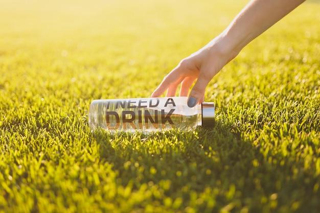 햇빛 잔디에 있는 푸른 잔디에서 음료가 필요하다는 문구가 적힌 신선하고 깨끗한 물을 병에 뻗은 손. 자연 질감 배경, 벽지입니다. 축구장 또는 스포츠 컨셉 디자인