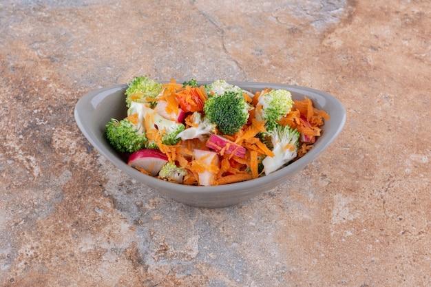 Ciotola ovale di insalata mista di verdure visualizzata sulla superficie di marmo
