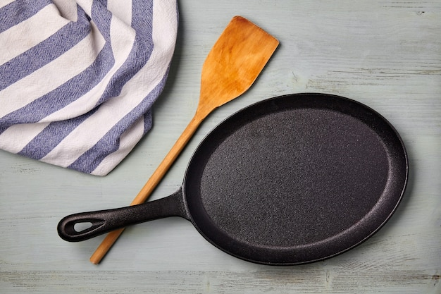 An oval cast iron frying pan with a wooden spatula and a tea towel on a blue wooden table. template for laying out a dish