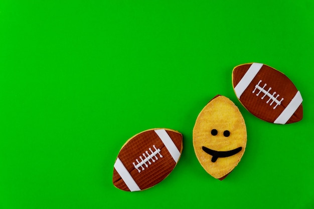 Oval cookie as an american football ball isolated on green background. top view.