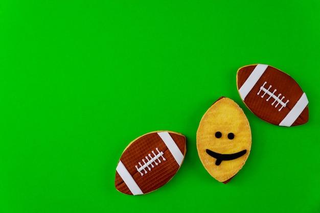 Овальное печенье как мяч для американского футбола, изолированные на зеленом фоне. вид сверху.