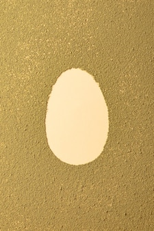 Oval easter egg silhouette made from matcha tea on green textured background minimalism