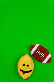 Oval funny face cookie as an american football ball isolated on green background. top view.
