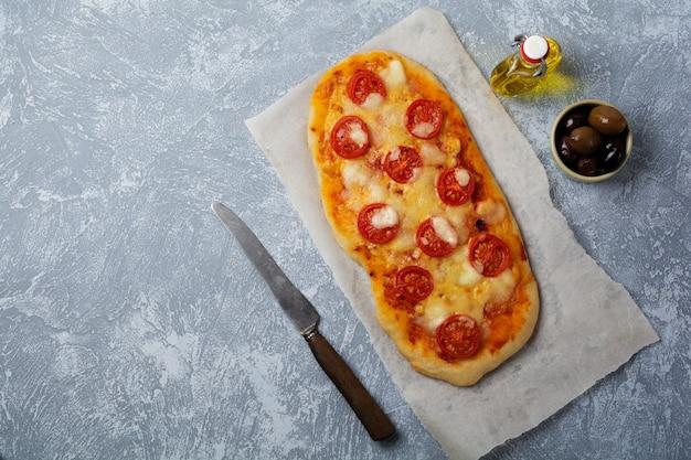 Oval italian pizza with tomato margarita on gray concrete.