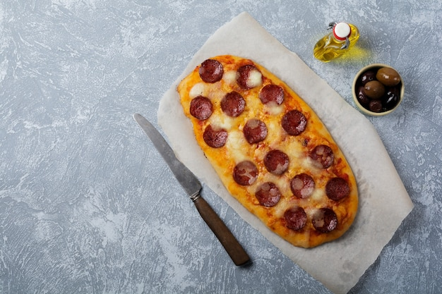 Oval italian pizza with tomato and salami pepperoni on gray concrete.