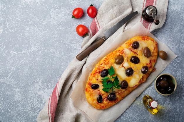 타원형 피자 그리스 올리브와 회색 콘크리트에 토마토.