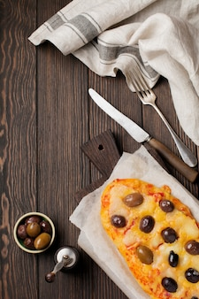 Oval pizza greek with olives and with tomato on dark wooden rustic.