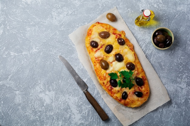 Oval pizza greek with olives and with tomato on gray concrete.