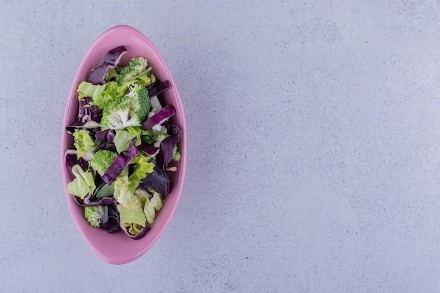 대리석 배경에 타원형 샐러드 그릇입니다. 고품질 사진
