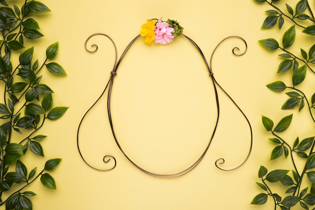 Oval shape frame with artificial rose on yellow wall with green leaves