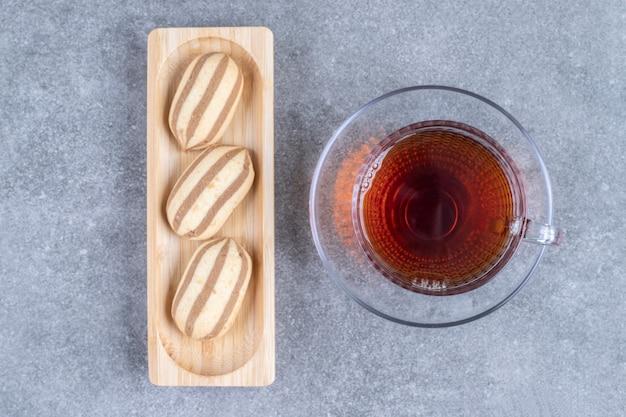 Печенье овальной формы на деревянной тарелке с чашкой чая