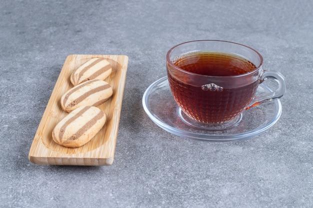 Biscotti a forma ovale su piatto di legno con tazza di tè