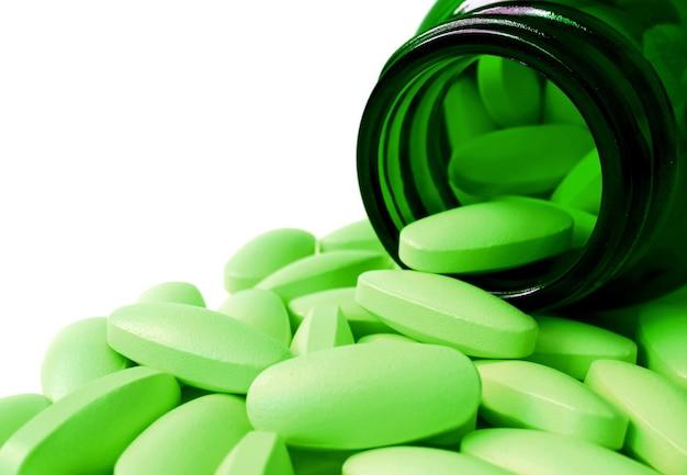 白で隔離される濃い緑色のガラス瓶から注がれた楕円形のライムグリーンの錠剤