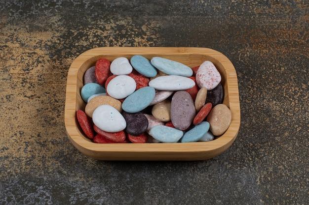 Каменные конфеты овальной формы на деревянной тарелке.