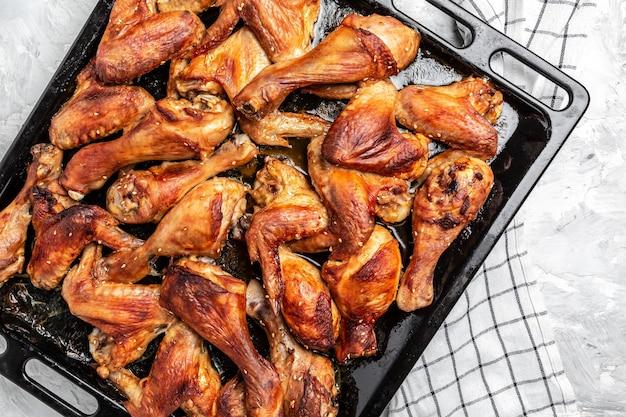 Запеченные в духовке куриные крылышки и ножки на противне