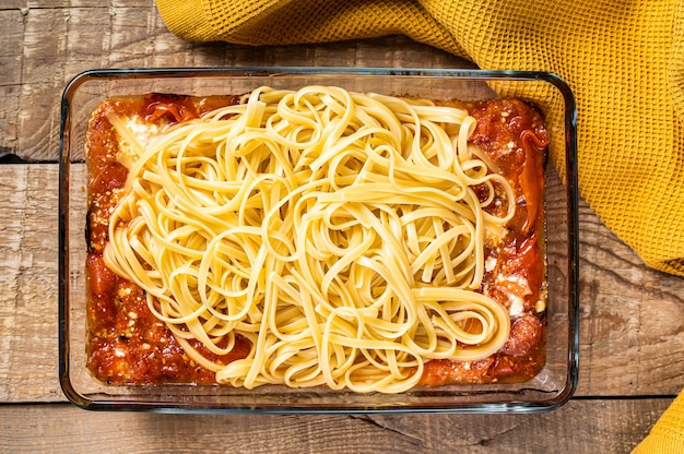 Oven baked feta spaghetti pasta in baking dish. wooden background. top view.