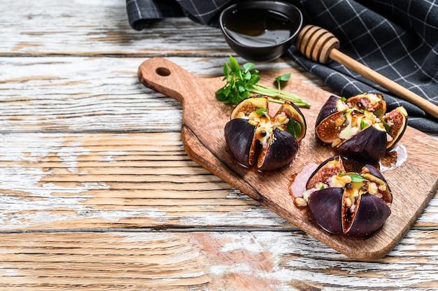 ゴルゴンゾーラ、ハーブ、蜂蜜のオーブンで焼いたイチジク。白色の背景
