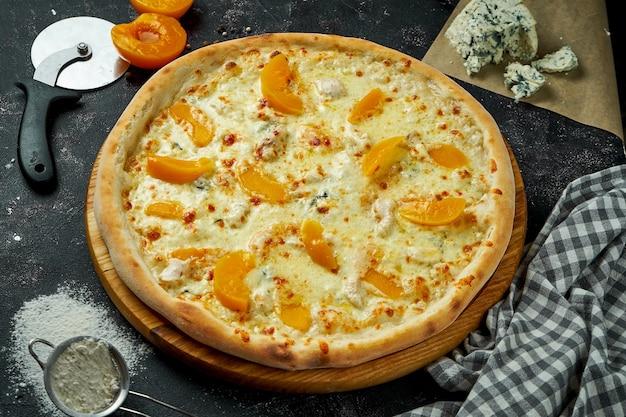Итальянская пицца, запеченная в духовке с 4 видами сыра и консервированным персиком в композиции с ингредиентами на темном столе. крупным планом вид