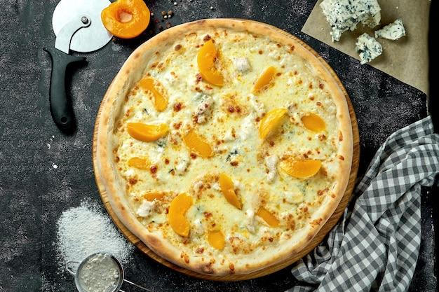 暗いテーブルの上に4種類のチーズと缶詰の桃を材料と組み合わせたオーブンで焼いたイタリアンピザ。上から見る