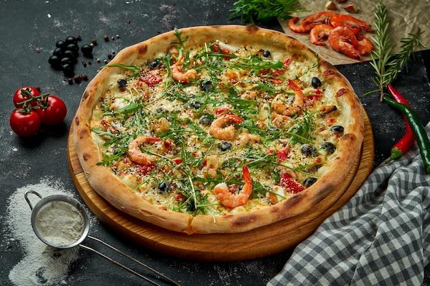 ソース、チーズ、ルッコラ、エビ、オリーブをオーブンで焼いたイタリアンピザに、暗いテーブルに材料を入れたもの。上面図。シーフードとピザ