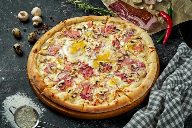 ホワイトソース、チーズ、ハム、マッシュルーム、生卵黄をオーブンで焼いたイタリアンピザに、暗いテーブルに材料を入れたもの。上からの眺め。ピザカルボナーラ
