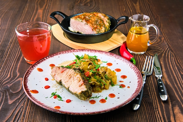 Oven-baked meat with braised cabbage and zucchini and hot spicy sauce