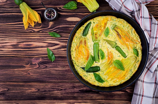 Oven baked omelette with flowers zucchini in pan on wooden background