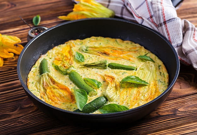 Oven baked omelette with flowers zucchini in pan on wooden background.