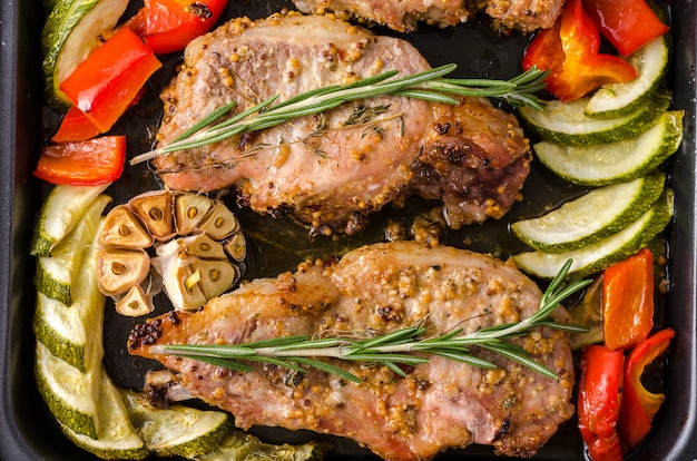 Oven baked pork entrecotes with bell pepper and zucchini on baking tray, on a dark background.
