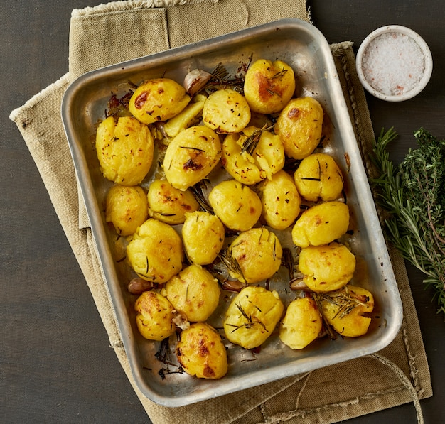 Oven baked whole crushed and crusty potato spuds with seasoning and herbs in metalic tray.