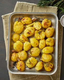 Oven baked whole crushed and crusty potato spuds with seasoning and herbs in metalic tray