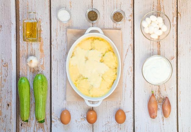 若いズッキーニをにんにくソースでオーブン焼き。木の床の白い皿の周りの食材のレイアウト