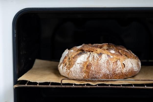 羊皮紙のオーブンパンは自家製パンサワードウパンを美味しくて自然な食べ物で焼きます Premium写真