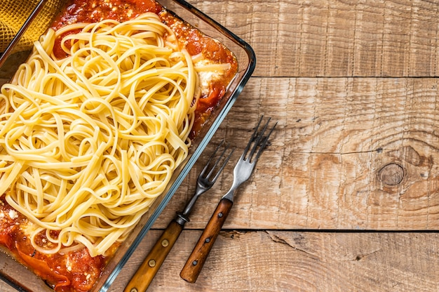 Oven roasted feta pasta with tomatoes in baking dish. wooden background. top view. copy space.