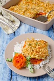 パンの皮の下ににんじんを添えたオーブンで焼いた魚の切り身。白ご飯の付け合わせに