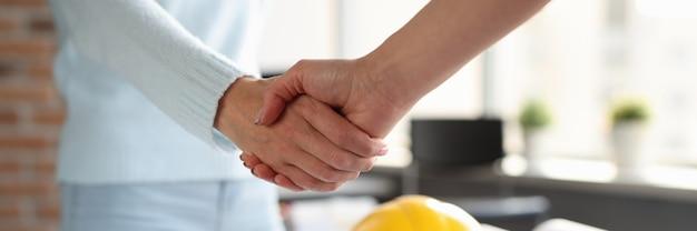 Дизайнер и заказчик пожимают друг другу руки над строительными эскизами