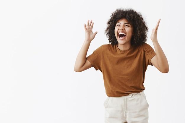 頭の近くの上げられた手で身振りで示し、左を見つめて大声で笑ってトレンディな茶色のtシャツのジェスチャーで過度に感情的な屈託のない幸せなスタイリッシュなモダンなアフリカ系アメリカ人女性