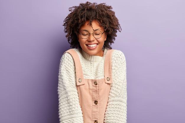 Более эмоциональная темнокожая женщина с кудрявыми волосами, чувствует радость и радость, приятно улыбается, одетая в белый джемпер и комбинезон, изолирована над фиолетовой стеной, услышав забавную шутку, выражает счастливые эмоции