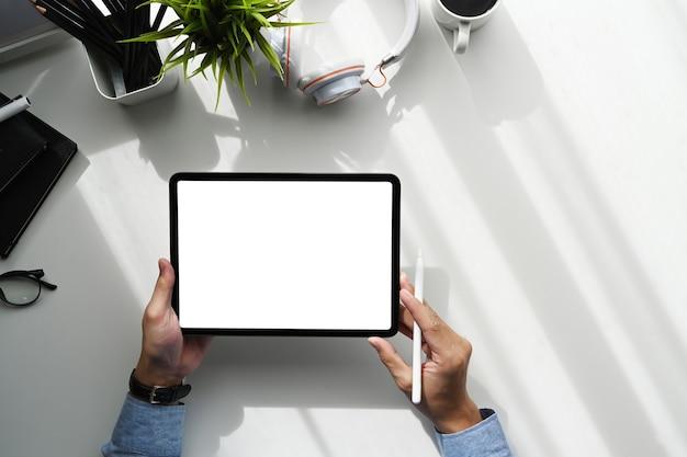白いテーブルの上のデジタルタブレットを使用してグラフィックデザイナーのオーバーヘッドショット。グラフィックディスプレイモンタージュの空白の画面。
