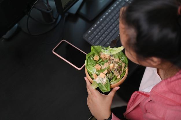 그녀의 직장에서 점심 시간에 신선한 샐러드를 데 여자 과체중의 오버 헤드 샷.