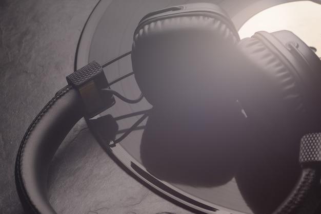 ビニールレコードのオーバーイヤーまたはオンイヤーヘッドフォン。黒の背景。クローズアップショット