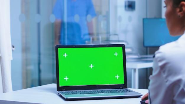 病院で利用可能なコピースペースを備えたラップトップを使用している医師の肩越しの映像。制服を着た看護師がキャビネットに到着。医療用clに展示されているクロマキー付きノートブックを使用した制服を着た医療従事者