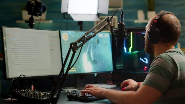 マイクとマウスを使用してrgbパワフルなコンピューターでデジタルスペースシュータービデオゲームをプレイするヘッドセットを備えたプロのストリーマーの肩越しの映像。オンラインビデオゲームをストリーミングするビデオゲーマーの男