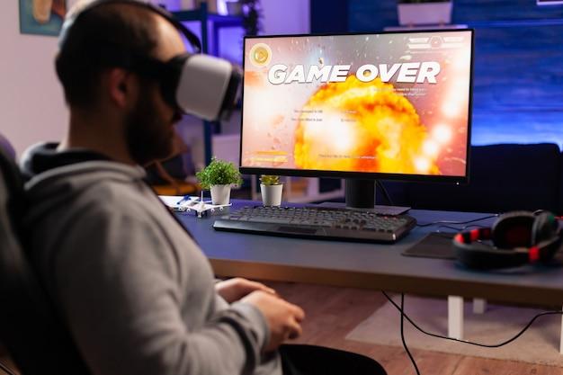 オンラインチャンピオンシップ中にバーチャルリアリティヘッドセットを身に着けている集中サイバープレーヤーの肩越しに。リビングルームで深夜にシューティングゲームの競争のためのコンソールを使用してプロゲーマーのためのゲームオーバー