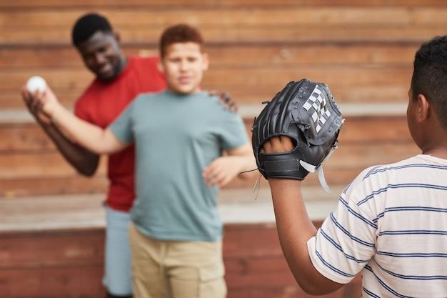 Вид через плечо на мальчика в бейсбольной перчатке, ловящего мяч, брошенный братом с помощью отца
