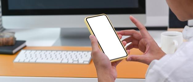 Через плечо вид бизнесмена, сидящего на рабочем месте и с помощью мобильного телефона.