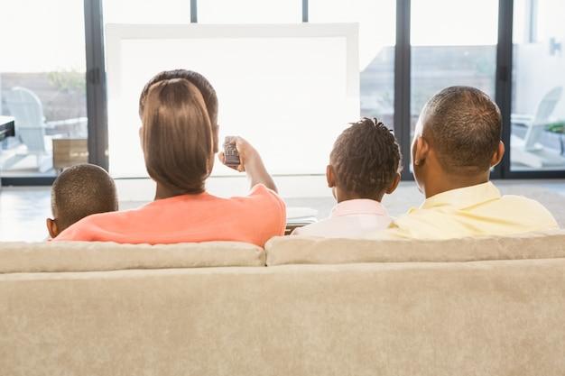 Над плеч зрения случайных семьи смотреть телевизор