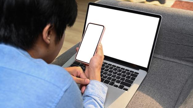 Вид через плечо человека, отдыхающего на диване, работающего с портативным компьютером и использующего мобильный телефон