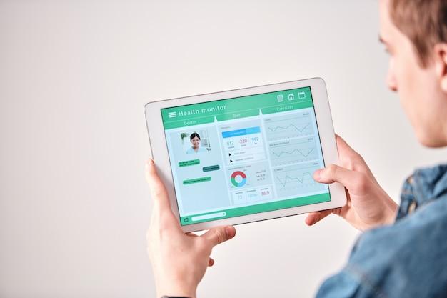 オンラインで医師とダイエットについて話し合っているときにデジタルタブレットを使用している男性の肩越しのビュー